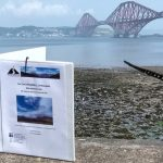 TW Reisgids op muurtje voor Firth of Forth Bridge Pol
